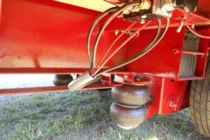 Close-up of the Air-Ride feature on the Red, 40 Foot, Pierced Frame, Lift Axle Trailer built by Custom Built Gooseneck Trailers